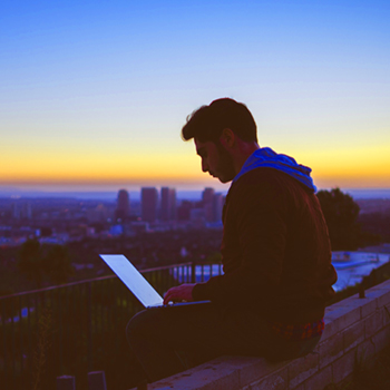 Young Man Uses Laptop on Rooftop