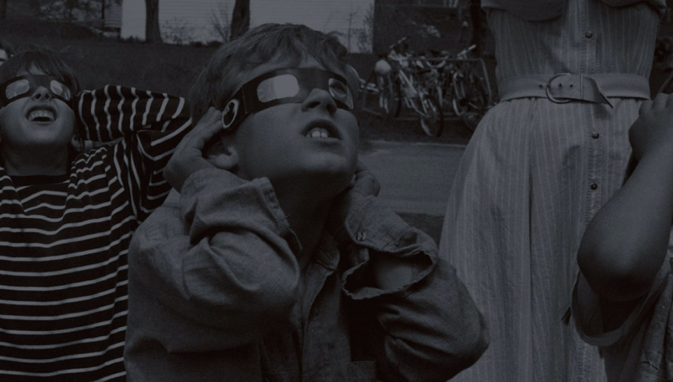 Black and white photo of children wearing glasses watching a solar eclipse