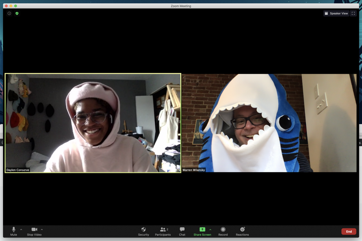 Daylen and Warren during a zoom call. Daylen wears a pinkhoodie, a matching pink beret, and glasses. Warren wears a shark costume and glasses.